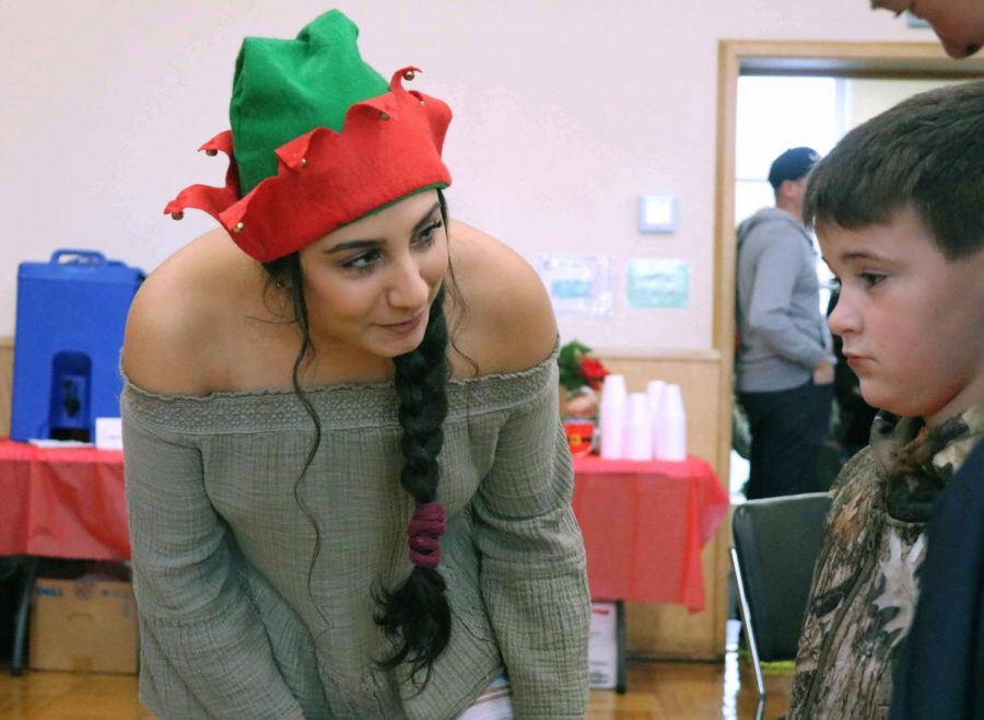 With an elf hat on, senior Zena Alshomali starts a conversation with a little boy who is waiting to see Santa Claus. Brunch with Santa was an annual event that is held in the Fenton Community Center.