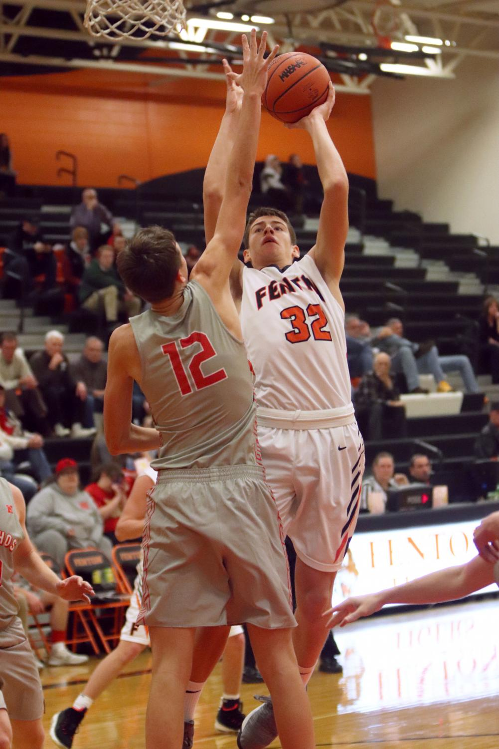 As Junior Kade Lookebill goes up for a basket, the holly defender attempts to block his shot. The boys varsity basketball team beat the Holly Bronchoas in overtime 44-40 on Jan. 4.