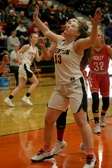 As she watches the ball, sophomore Kyla Lynch guards the basket. The girls varsity basketball team beat the Holly Bronchos 48-45.