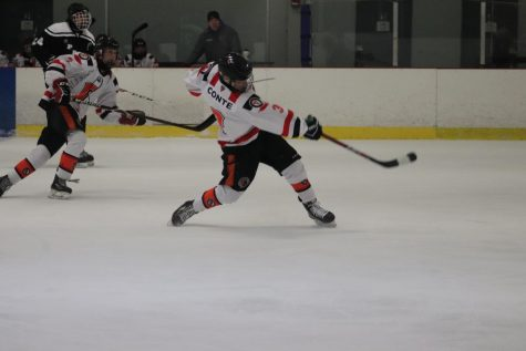 Senior Dylan Conte shoots the puck towards the opposing net. In the end the team won with a score of 3-1 on Jan. 9.