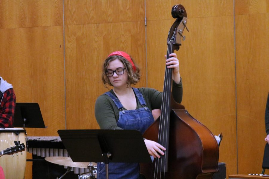 Plucking her standing base, senior Hanna Ferguson plays wish the FHS jazz band. On Dec. 17, the jazz band and choir hosted a Christmas concert for the school before winter break.