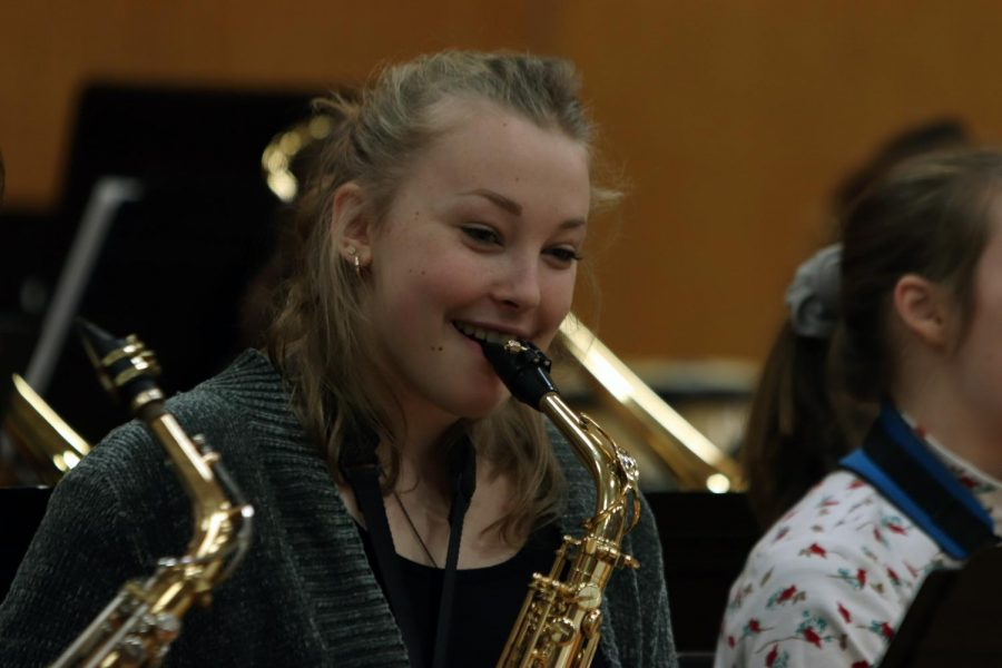 As the Christmas Concert is in session, junior Reese Strawsburg smiles in happiness enjoying the show. The choir and band perform every year for the school to get the students excited about christmas.