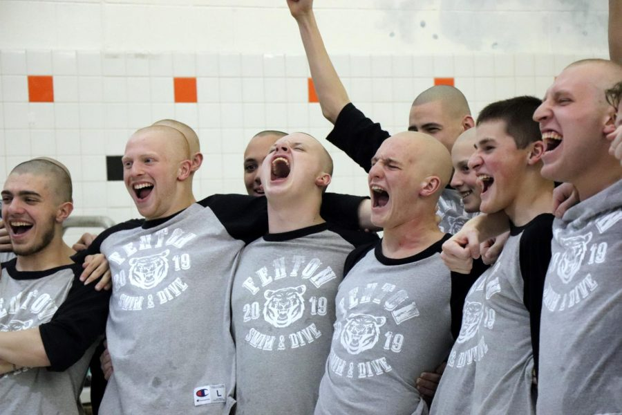 Screaming in victory, the Boys' swim team accepts their Flint Metro's award. This was the seniors' last home meet.