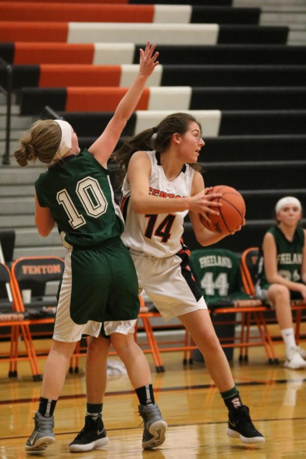 An opponent attempts to block freshman Josie Cherneys pass to her teammate. On jan. 23, the freshman girls basketball team played against Freeland at home.