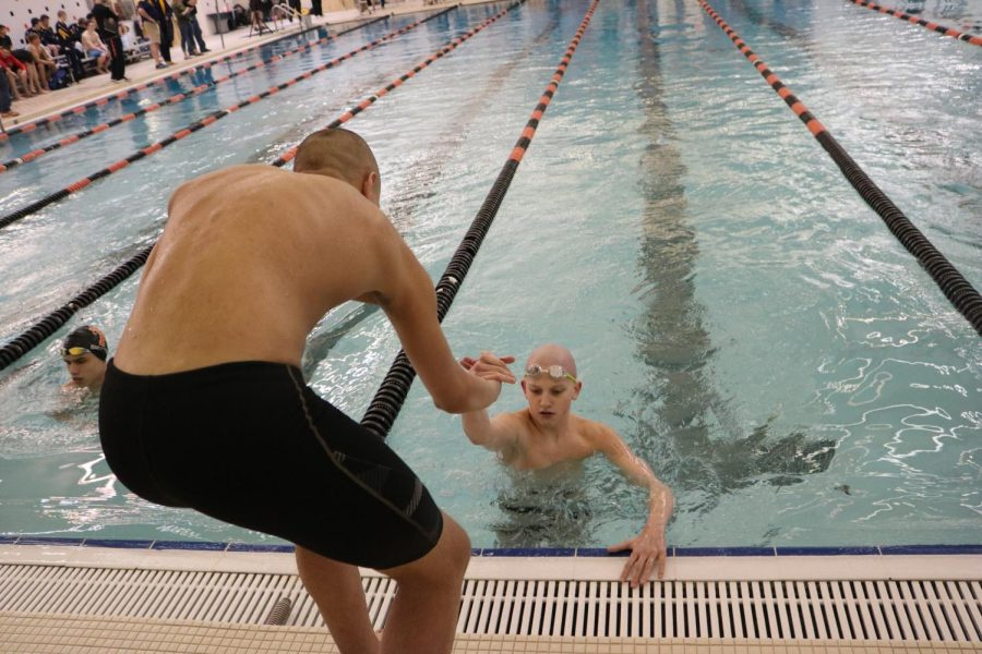 After finishing his heat, freshmen Joel Fries gets helped out of the pool by one of his teammates. The Fenton Boy swim team went on to win the Flint Metro League title on Friday Feb. 22.