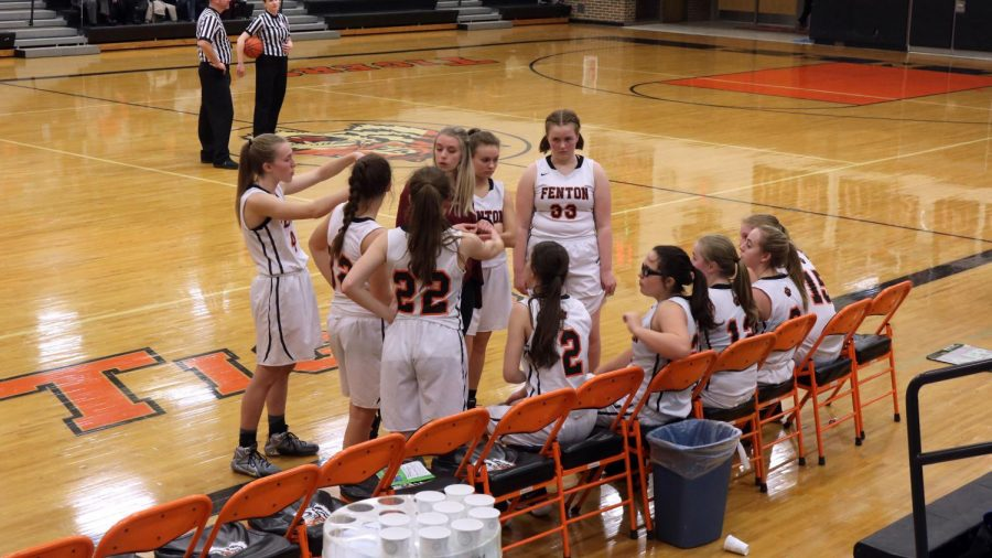 Fenton girls J.V. basketball team work out a game plan for action. Sophomore Mallory Lehmann makes gestures to represent the game plan.