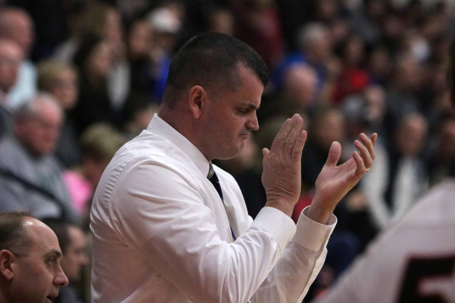 After the outcome of a play, varsity basketball coach Chad Logan claps and cheers for the varsity boys basketball team.  The boys basketball team played Linden on Jan. 18.