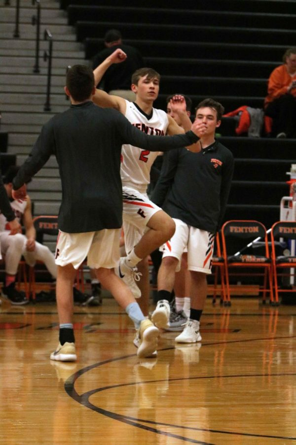 While his name is announced to the spectators, junior Addison McIntosh performs his regular game hand shake with senior Nick Cairnduff.  The boys varsity basketball team played Owosso on Feb. 5.