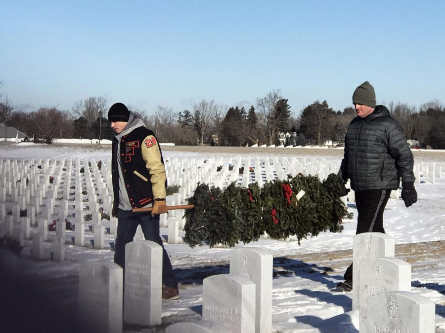 Volunteers join together at Great Lakes National Cemetery to take wreaths off of tombstones. On Jan. 26, some of these volunteers were Fenton high school boys basketball players. Varsity Basketball Coach Chad Logan and Junior Addison McIntosh carry wreaths to the truck.