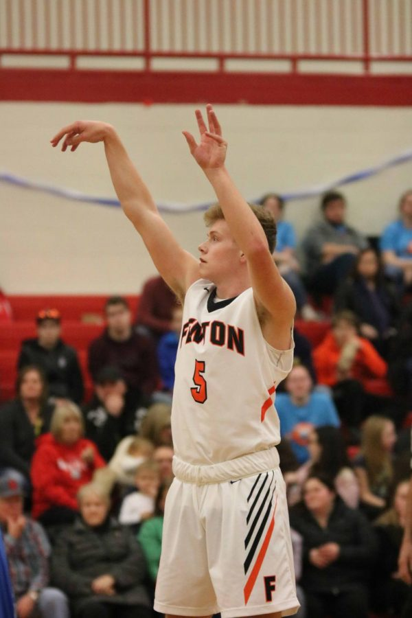 Anticipating the outcome of a free throw, junior Alec Kussro watches the ball go into the hoop.  The boys varsity basketball team played Holly on Feb. 8.