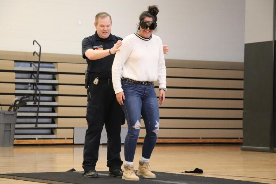 A Police Officer guides senior Delaney Miesch while she wears goggles that simulate being intoxicated. Officers gave students an intoxication test to demonstrate how they test drivers.