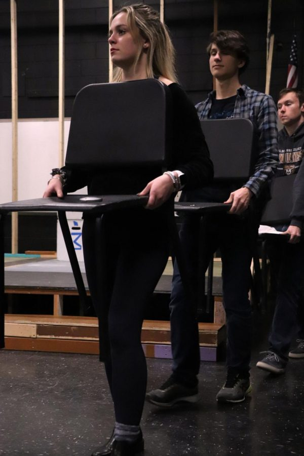 Senior Alexandra Marsee and fellow IB theater students carry chairs as a prop for a scene. On Feb. 13, a practice was held for the upcoming IB theater play Columbinus.
