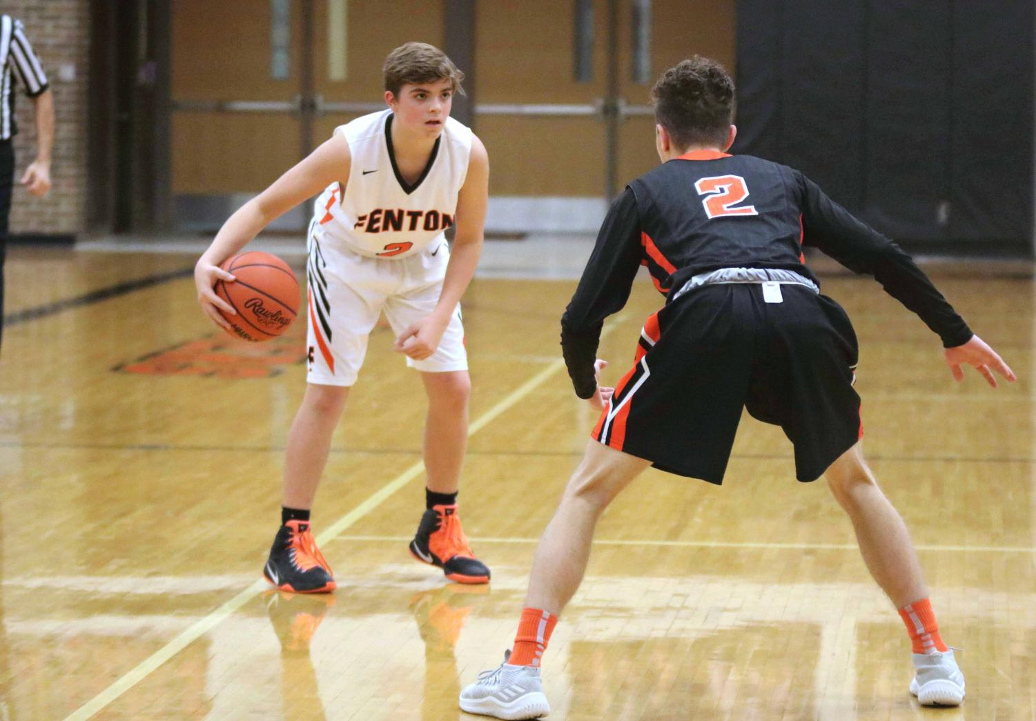 Dribbling the ball, freshman Seth Logan faces against a Flushing High basketball player. Fenton JV boys lost 36-32.