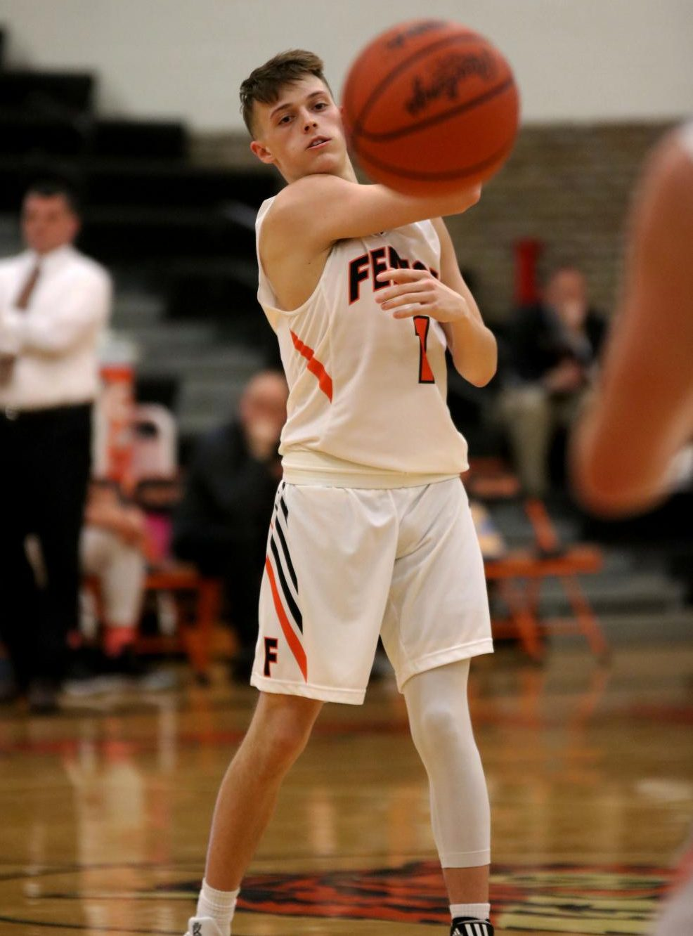 As the boys varsity basketball team plays Owosso, junior Trent DeGayner passes the ball to his teammate. The boys varsity basketball team's last home game is Feb. 22 against Linden.