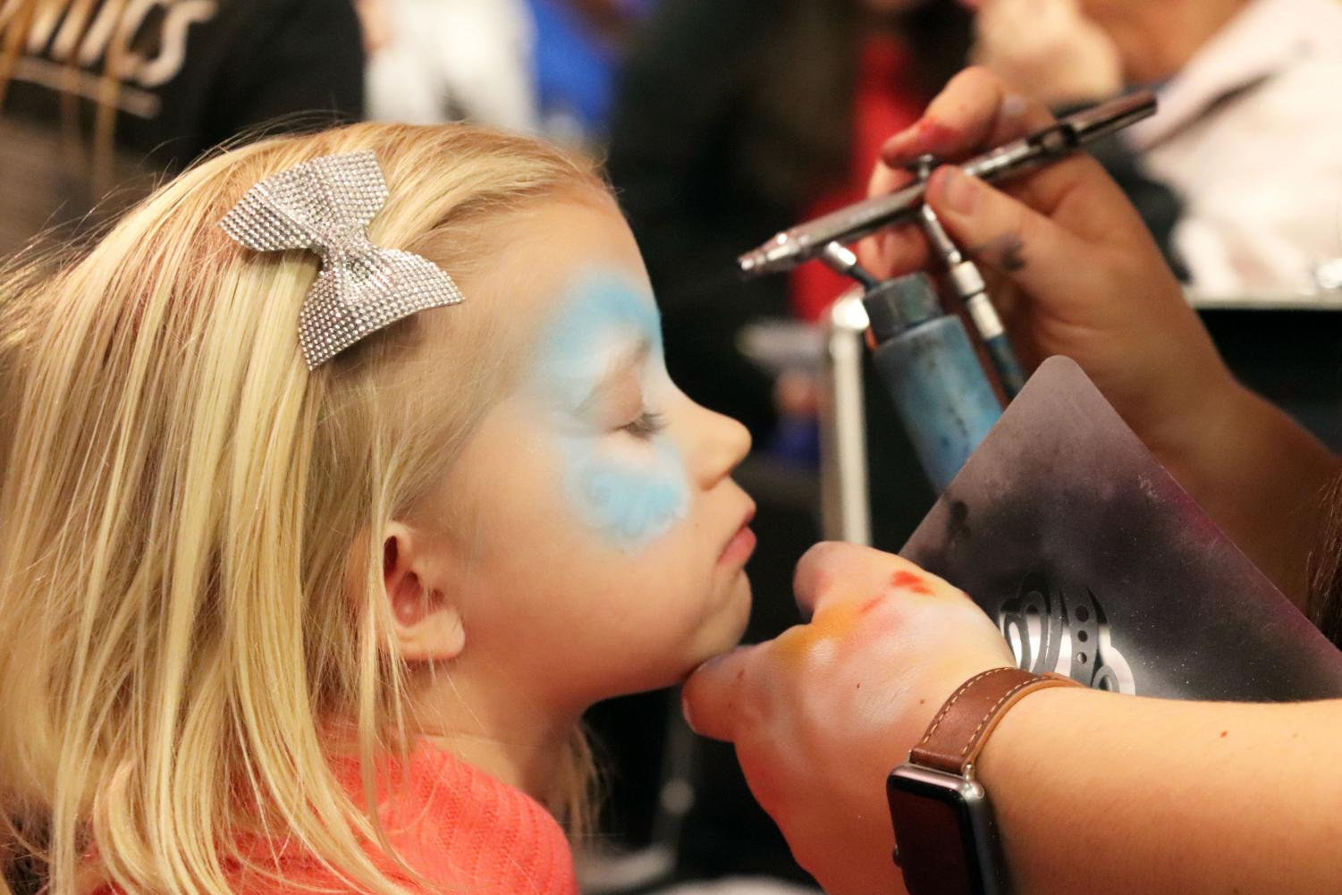 While attending the Fenton Expo with her mother Kristin McDowell, Sinéad McDowell gets face paint at the Dr. Wax Orthodontics booth. The Fenton Expo had many businesses in the Fenton High School with many activities for kids like face painting.