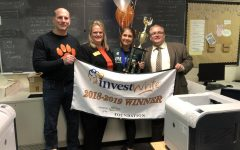Senior Cami Tiemann and Finance teacher Bruce Burwitz pose with representatives from Investwrite after Tiemann was awarded eighth in the nation for her essay. All of Burwitz's classes wrote a paper earlier in the year giving advice to entrepreneurs about how to invest their money.