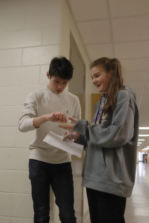 Q-tip in hand, sophomore Desmond Braham swipes on the petri dish held by fellow sophomore Coral Lefever with bacteria collected from the floor. Biology students collected bacteria samples around the school to monitor its growth in agar.