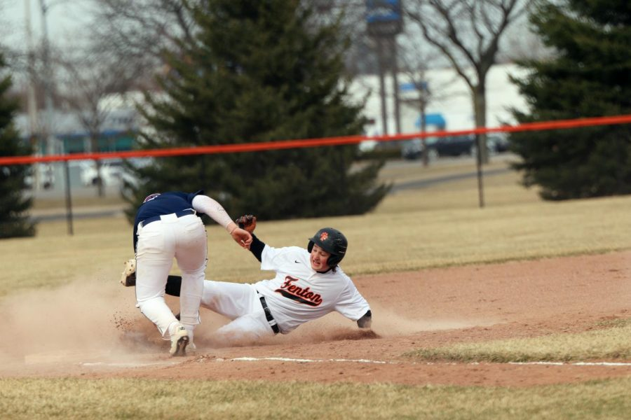 Sliding in to touch the base, sophomore Lucas Shelton, avoids getting tagged out. The JV baseball boys played against their Saline opponents.