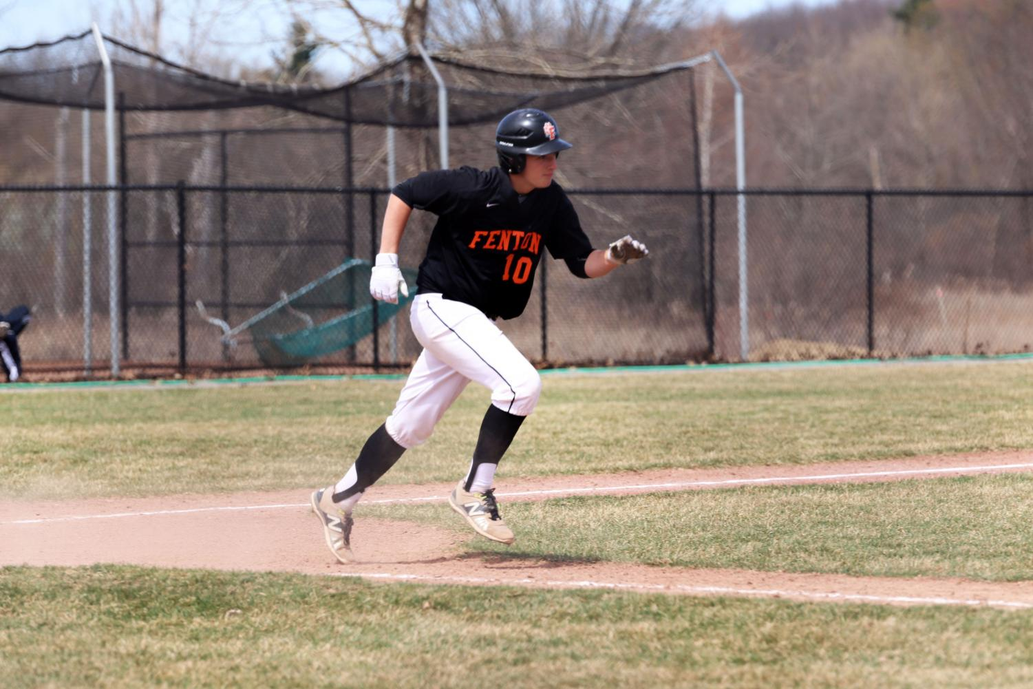 Sophomore Gannon Welch (10) runs to first base after hitting the ball. Fenton JV baseball played against Hartland on April 13th.