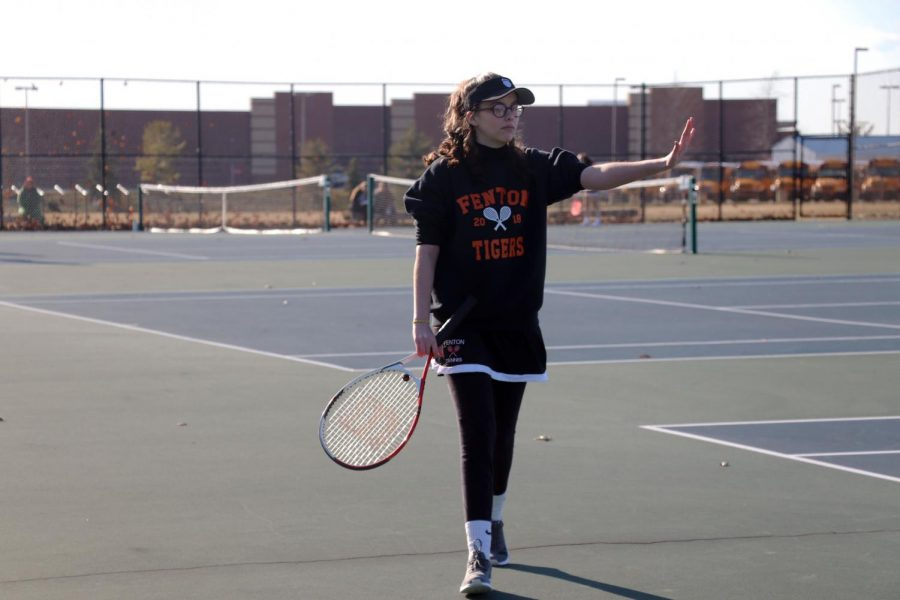 Fenton junior varsity girls tennis team plays against Powers Catholic High School. Sophomore Bridget Maxwell holds her hand up as she grabs a ball to start the match.