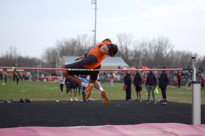 Eyeing his landing, freshman Ethan Bright jumps at the Flint Metro League meet at Swartz Creek. The boy's track team beat both Flushing and Swartz Creek.