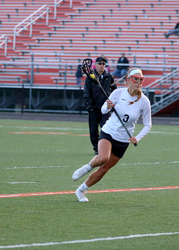 Running down the field, senior Sarah Reuschlein tries to get to the goal. The girls varsity lacrosse team beat Waterford Kettering, 19-3.