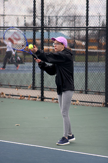 To begin her match, sophomore Bridget Maxwell prepares to serve the ball. The JV girls tenni steam played the Flushing Raiders on April 25.