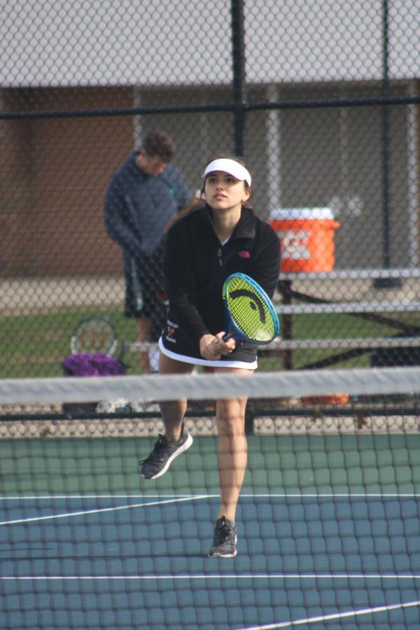 After returning the ball, freshman Alyssa Andrews watches as it goes to her opponents. Andrews and her partner, freshman Makena Fisher, beat Holly on April 23rd.