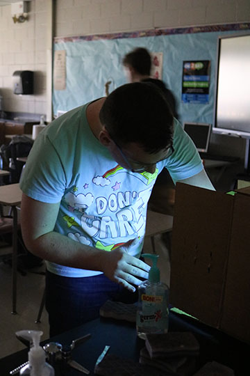 While he carries out his lab, sophomore Jacob Gurnsey puts his hands under a blacklight. The Biology classes tested different methods of washing hands.