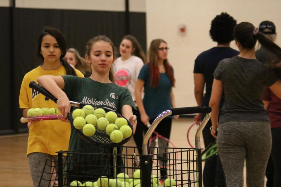 Tossing tennis balls into the ball cage freshman Grace Woodruff cleans up the gym floor after the jv girls tennis teams warm up. The girls first tennis game was on Apr. 3 against Powers Catholic High School.