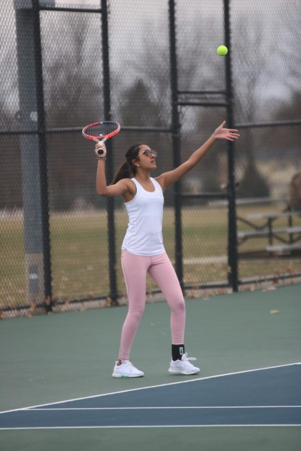 Throwing the ball up in the air, sophomore Sarasee Kiran plays a singles match. The girls varsity tennis team played against South Lyon on April 10.