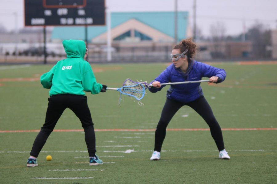 While practicing new techniques, junior Taron Masi defends the ball from her partner.  The girls varsity lacrosse team plays on April 5 at Powers Catholic High School.