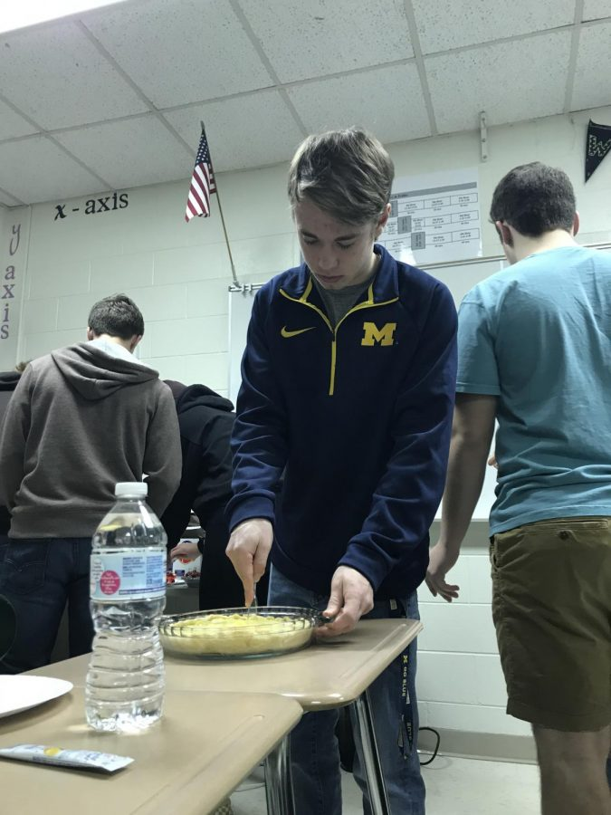 During a Pi day celebration, senior Logan Lake cuts into a pie for his class.  The Algebra 2 (Year 2) classes celebrated Pi day by eating pie and solving a Pi related equation.