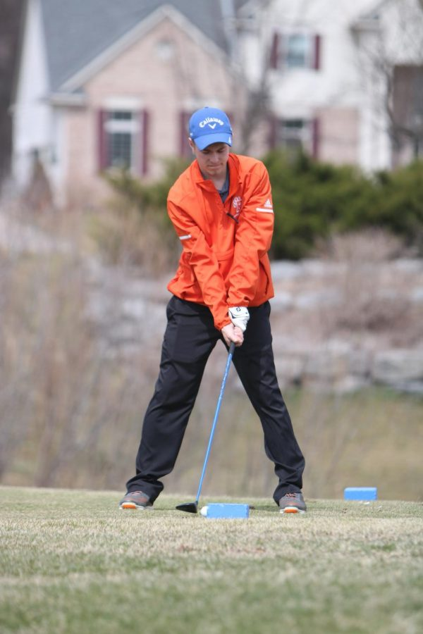 Eyes on the ball, senior Logan Lake gets ready to hit his tee shot. The varsity boys golf team took 3rd out of 21 teams at the Lapeer Tune-Up on April 12th.