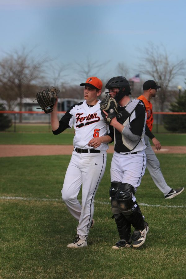 While they walk to the dugout after fielding, sophomores Brendan Alvord and Logan Angel discuss strategy.  The varsity baseball team plays on April 25 at Swartz Creek.