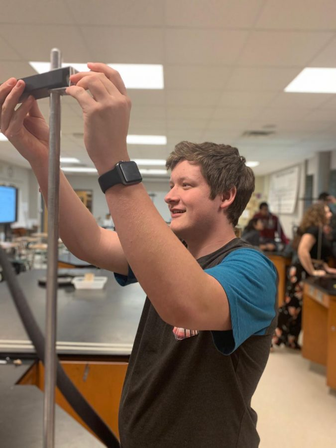Adjusting the height of a bar, junior Tim Dingman builds a rollercoaster with his lab group. Conceptual physics teacher David Sturm had students build a rollercoaster to study kinetic and potential energy.
