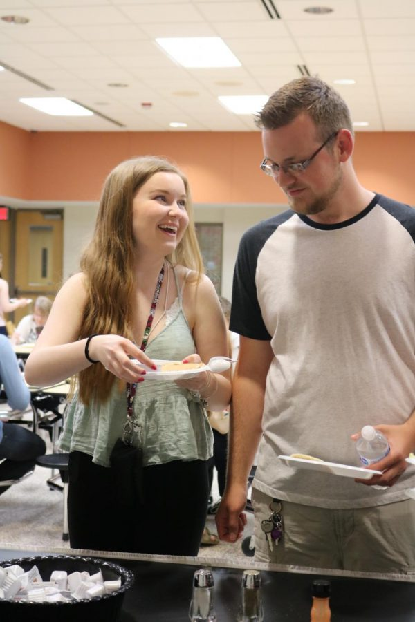 Standing in line, seniors Lauren Beck and Tucker Bain laugh with their friends. The Class of 2019 gathered for senior breakfast on May 29.