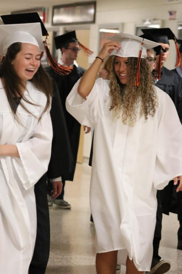 As seniors Kirty Foor and Drew Follett walk down the hall to Honor award assembly they laugh together. They got their diplomas on june 2 at the graduation ceremorny.