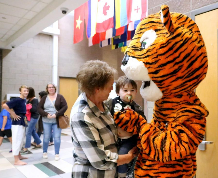 Wearing the Fenton Tigers mascot, sophomore Cameron Carlson holds a child for a picture. On Sept. 7, key club volunteered at AGS for the first ever pancake breakfast, where parents and kids ate pancakes made by a record-holding cook and played games in the gym.