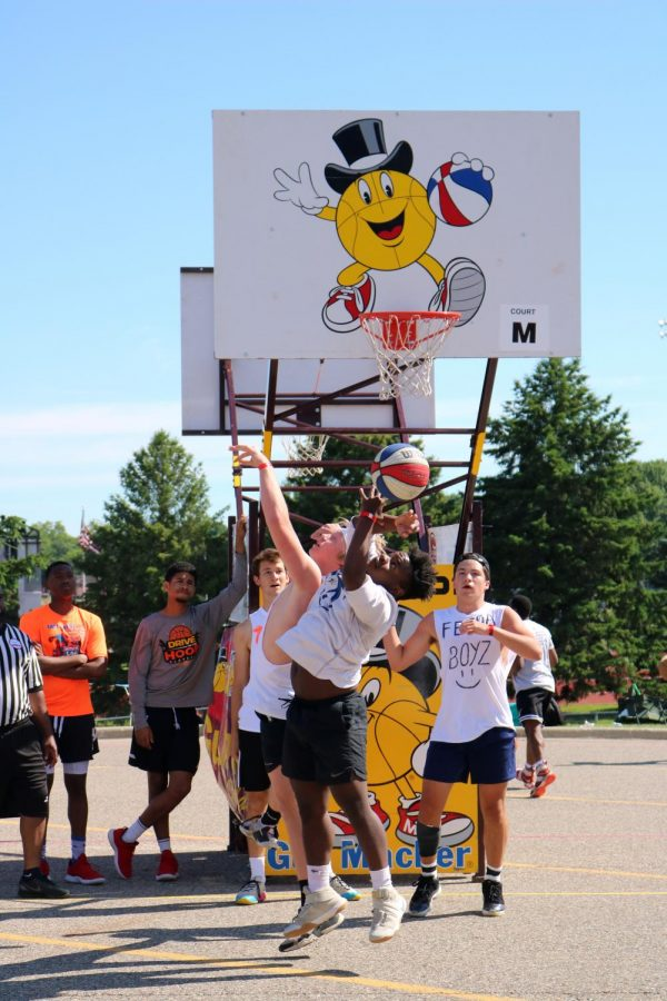 Senior Jack Gundry attempts to block opponent, senior Amari Westbrook from scoring. On June 23, the annual Gus Macker basketball tournament was held at Linden High.