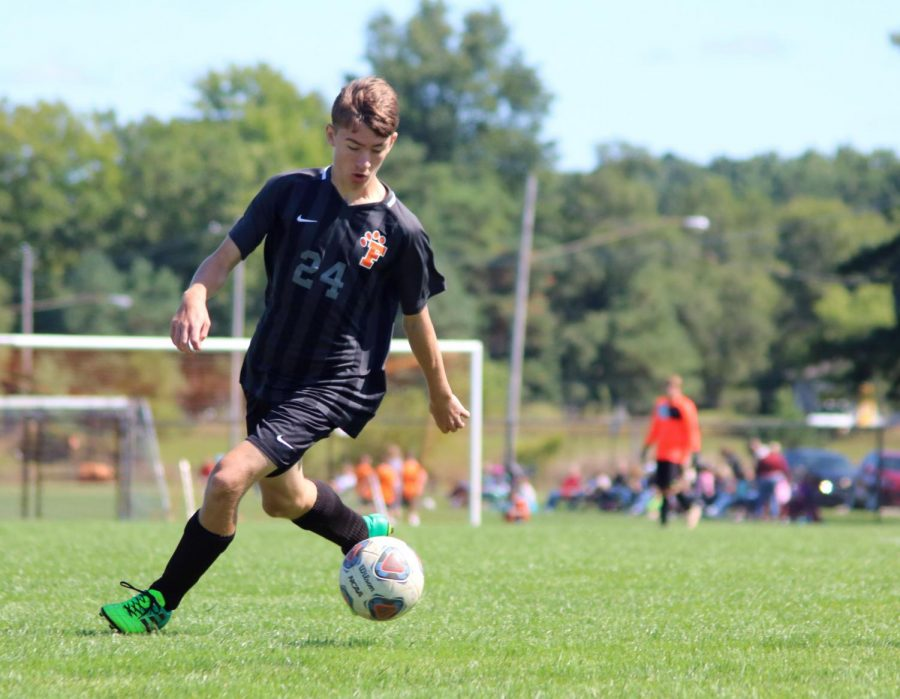Junior Christopher Lafave prepares to pass the ball to a teammate. On Sept. 14, the varsity boys soccer team played Detroit Catholic Central at home, tying 2-2.