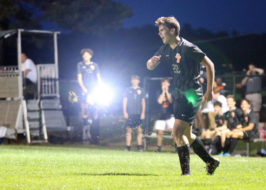 Junior Zander Fulton kicks the soccer ball to a teammate, grass flying into the air from the impact. On Sept. 16, the varsity boys soccer team played Kearsley at home, winning 5-0.