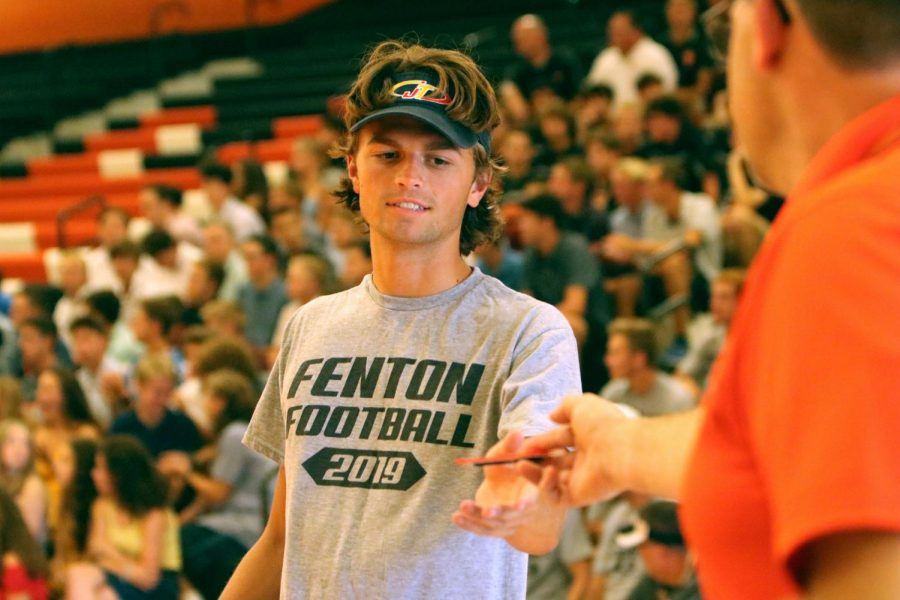 Being recognized for sports achievements in front of peers and parents, senior Ryan Miller accepts an award. On Aug. 21, student athletes and parents attended the fall Meet the Team to acknowledge students and their sports.