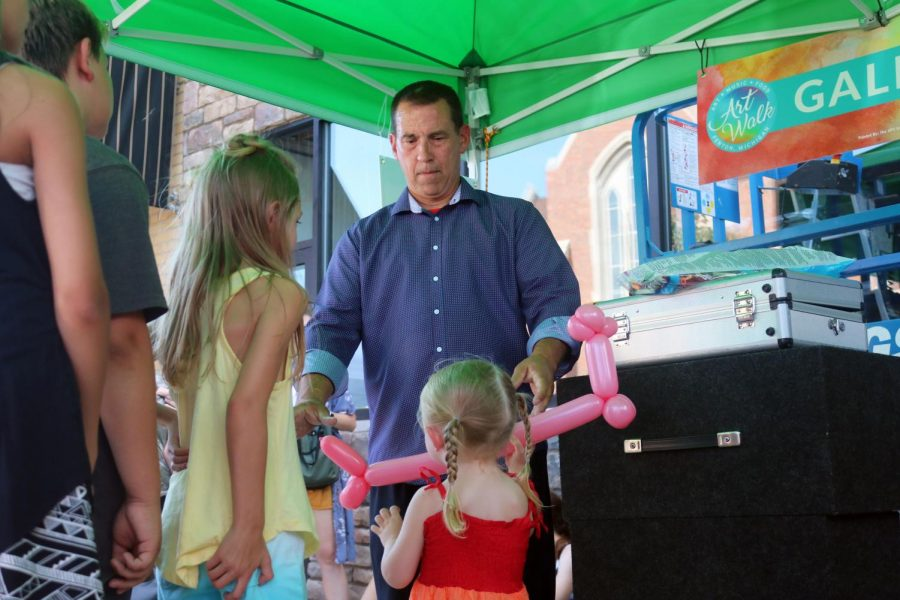 Children wait in line for balloon animals by a balloon artist at the Fenton Art Walk. On July 13, there were galleries and venders in downtown Fenton for the Art Walk.