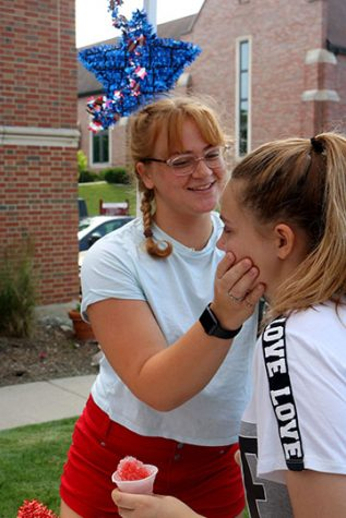 As the parade begins, senior Zoe Simmerman gives a child a temporary tattoo. Simmerman was volunteering with the Fenton United Methodist Church.