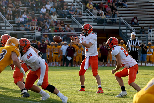 After the center snaps the ball, junior Dylan Davidson prepares to catch it. The Tigers played the Davison Cardinals.