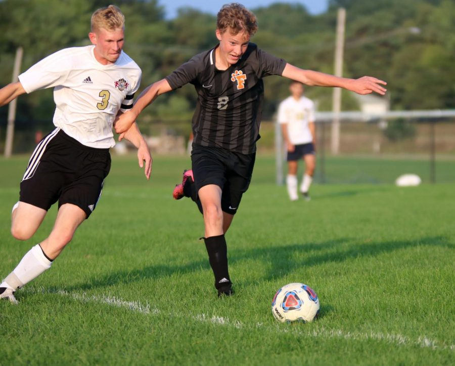 Senior Mitchel Scheer races his opponent to the ball during a game. On Sept. 9, the varsity boys soccer team played Corunna at home, winning 5-2.