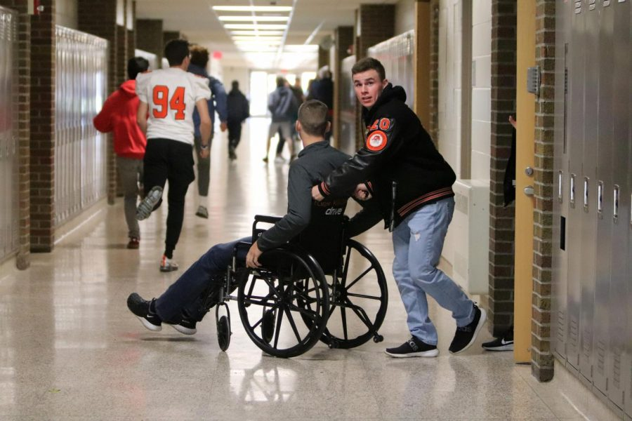 Simulating an intruder drill, senior Brady Triola pushes senior Kade Lookebill on his wheelchair as they evacuate the building. ALICE training took place on Oct. 18.