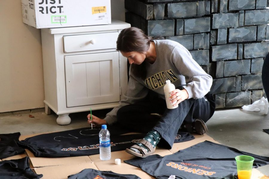 In deep concentration, senior Lilly McKee paints the zero in 2020 on her Powderpuff sweatpants.  The Powderpuff game between the senior and junior girls is on Monday, Oct. 7.
