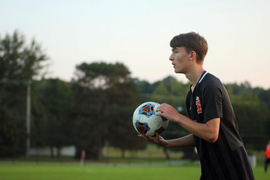 Junior Christopher Lafave looks for a teammate to throw the ball to from the sideline. On Oct. 2, the boys varsity soccer team played Flushing at home, winning 5-0.
